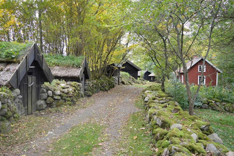 Små svarta stugor står längst en väg kantad av stengärdsgårdar.