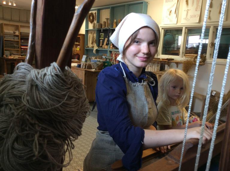 En kvinna i tidsenliga kläder visar ett barn hur man bereder lin till tråd.