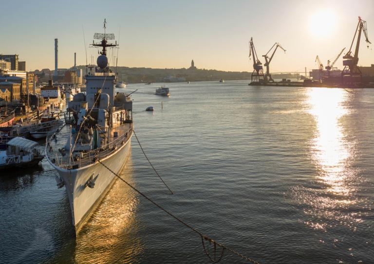 Solnedgång över Göteborgs hamn med Maritimans skepp i vänster kant och Eriksbergskranarna till höger.