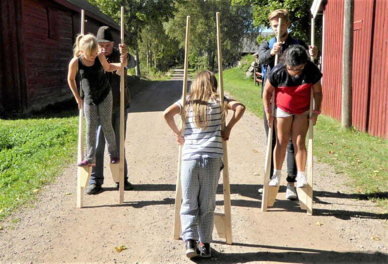 Barn går på styltor på Kulturreservatet Vallby Sörgården