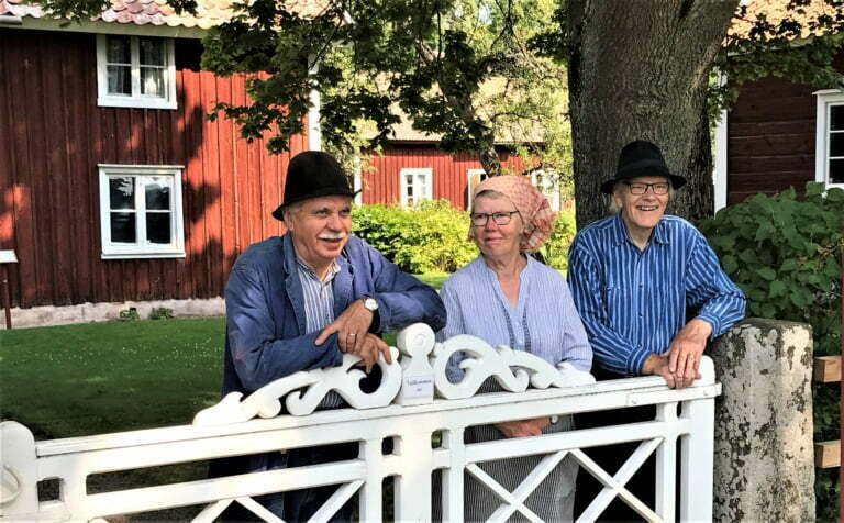 Två män och en kvinna i blåvitrantiga kläder, hatt och huckle står och hänger på grinden in till Vallby Sörgården.