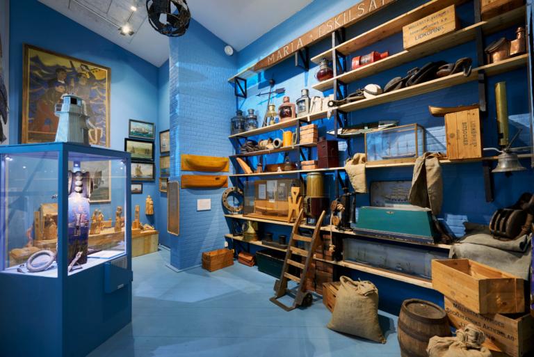 Utställningsrum med bått golv och väggar och hyllorna fyllda av maritima föremål.