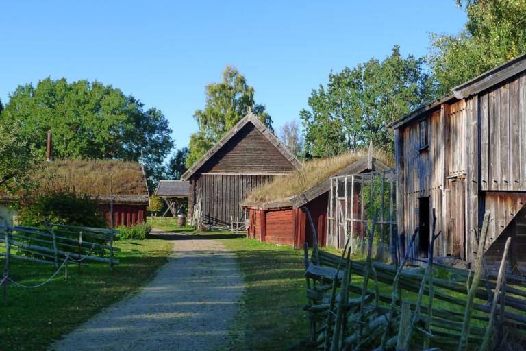 Flera äldre stugor ligger längst en gata omgärdad av gärdsgårdar i trä.